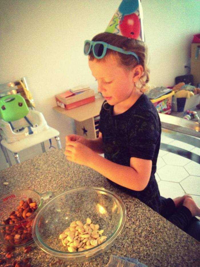 My little party animal wearing the hat and glasses from his cousins party yesterday (he wore them like this all day) while helping me  make almond milk.